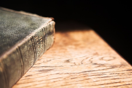 """verse: Leather covered old bible lying on a wooden table in a beam of sunlight Shallow Depth of field – Focus on Text """"Holy Bible"""" Stock Photo"""