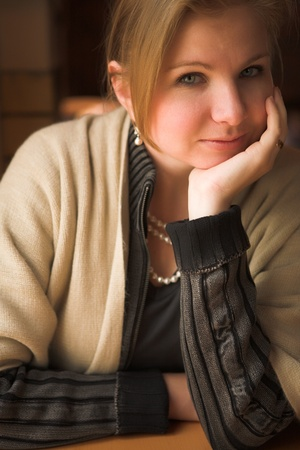 Blonde caucasian adult woman sitting next to a natural light window in the beginning of winter. Shallow Depth of Field photo
