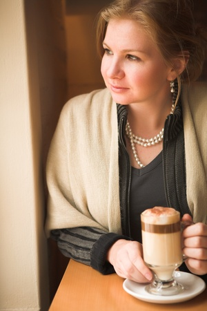 Blonde caucasian adult woman sitting next to a natural light window in the beginning of winter drinking hot cafe latte. Shallow Depth of Field photo