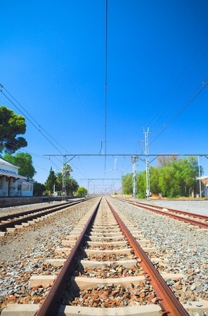train tracks: Perspective train tracks at the station of Matjiesfontein in the Western Cape, South Africa on a sunny, blue sky day