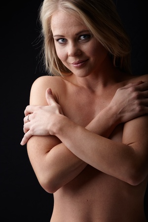 Nude young adult caucasian woman with blonde hair and blue eyes on a dark background Stock Photo - 11706060
