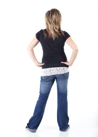 Cute and active young adult caucasian woman wearing a black top and blue jeans and with short brunette hair on a white background. Not Isolated photo