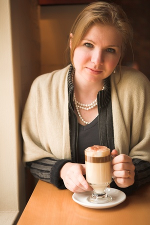 Blonde caucasian adult woman sitting next to a natural light window in the beginning of winter drinking hot cafe latte  Shallow Depth of Field photo