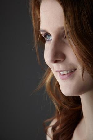 fair skin: Retrato de una joven pelirroja cauc�sico adulto con ojos verdes y piel muy blanca sobre un fondo gris neutro