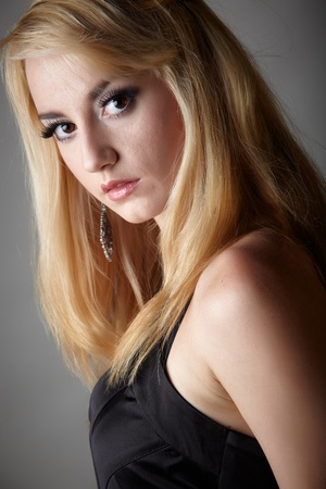 lbd: Young adult caucasian woman with blonde hair and prominent jewelry on a neutral grey background with a little black dress and big brown eyes