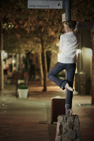 Young adult blonde ballerina dancing at night under signs and lamp posts in a general urban area  Shallow Depth of Field photo