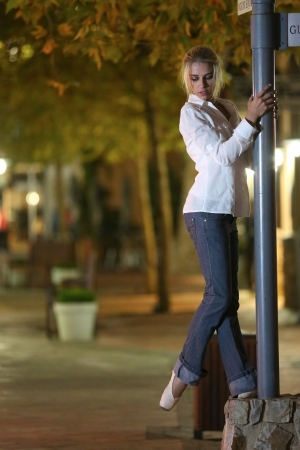 pointe: Young adult blonde ballerina dancing at night under signs and lamp posts in a general urban area  Shallow Depth of Field Stock Photo