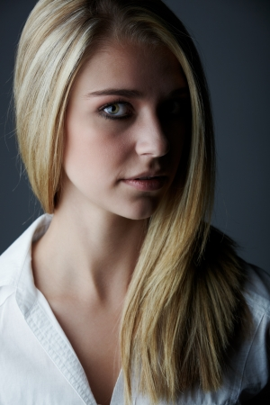 Young adult caucasian woman with long blonde hair and green eyes wearing a plain white shirt with flawless skin and natural makeup  Stock Photo - 13644584