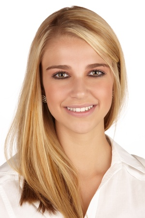 Young adult caucasian woman with long blonde hair and green eyes wearing a plain white shirt with flawless skin and natural makeup  Stock Photo