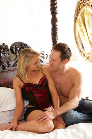Young and fit caucasian adult couple in an embrace. Semi-nude and topless on a bed in a light bedroom with the woman wearing a sexy red and black lace corset and the man wearing only blue jeans. Stock Photo