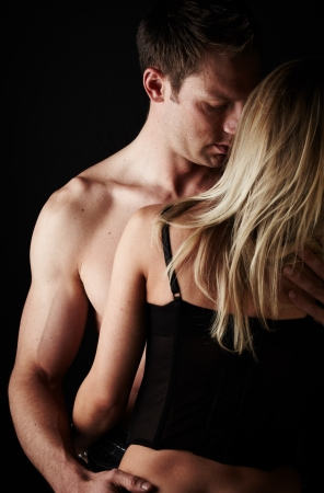 Young and fit caucasian adult couple in an embrace. Semi-nude and topless against a dark background with the woman wearing a sexy red and black lace corset.. Stock Photo