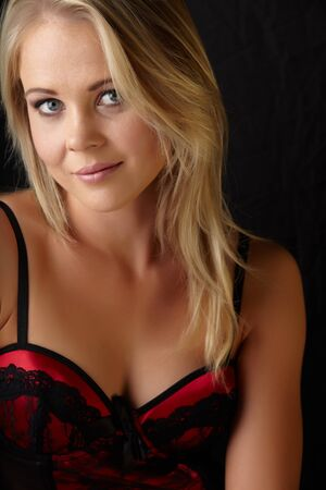 Young and fit caucasian adult woman in a sexy black and red lace corset against a dark background . photo