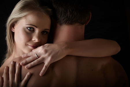 Young and fit caucasian adult couple in an embrace. Semi-nude and topless against a dark background . Stock Photo - 13644599