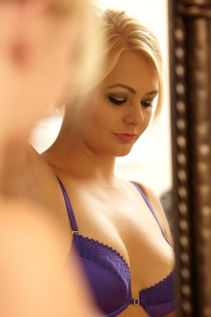 undressed: Young adult caucasian woman in purple lingerie looking at herself in a wall mirror while holding her blonde hair up with one hand  Stock Photo