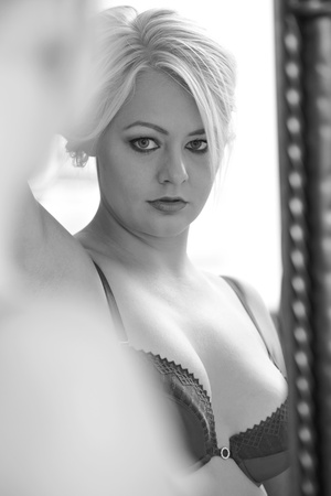 Young adult caucasian woman in purple lingerie looking at herself in a wall mirror while holding her blonde hair up with one hand  Black and White image Stock Photo - 13644565