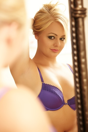 Young adult caucasian woman in purple lingerie looking at herself in a wall mirror while holding her blonde hair up with one hand  Stock Photo