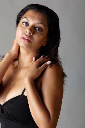 voluptuous: Giovane donna voluttuosa adulta indiana con lunghi capelli neri che indossa un abito nero e blu, lenti a contatto colorate su uno sfondo grigio neutro etnia mista