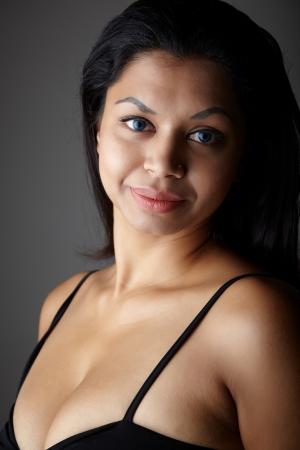 voluptuosa: Joven mujer voluptuosa para adultos de la India con el pelo largo y negro vistiendo ropa interior negro y lentes de contacto coloreadas azules en un fondo gris etnia mixta neutra