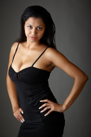 fuller figure: Young voluptuous Indian adult woman with long black hair wearing a black dress and blue coloured contact lenses on a neutral grey background  Mixed ethnicity Stock Photo