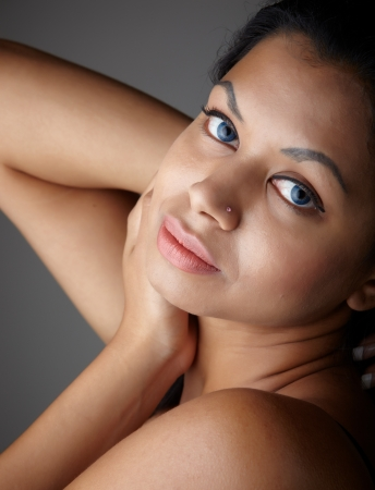 Young voluptuous Indian adult woman with long black hair wearing black lingerie and blue coloured contact lenses on a neutral grey background  Mixed ethnicity photo