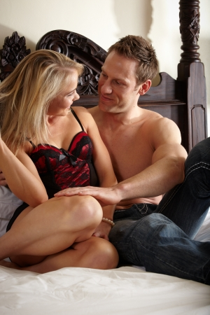 Young and fit caucasian adult couple in an embrace  Semi-nude and topless on a bed with the woman wearing a sexy red and black lace corset and the man wearing only blue jeans