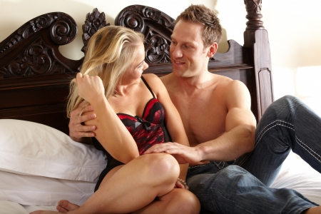 Young and fit caucasian adult couple in an embrace  Semi-nude and topless on a bed with the woman wearing a sexy red and black lace corset and the man wearing only blue jeans  Stock Photo - 13872237