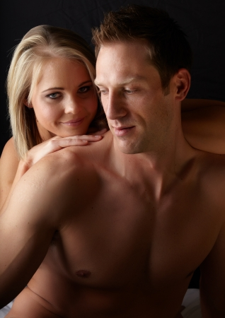 Young and fit caucasian adult couple in an embrace  Semi-nude and topless against a dark background  Stock Photo - 13872207