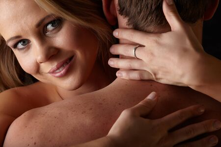 Young and fit caucasian adult couple in an embrace  Semi-nude and topless against a dark background Stock Photo - 13872214