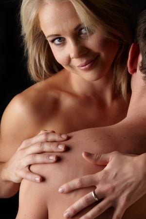 Young and fit caucasian adult couple in an embrace  Semi-nude and topless against a dark background   Stock Photo - 13872222