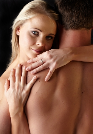 Young and fit caucasian adult couple in an embrace  Semi-nude and topless against a dark background Stock Photo - 13872245