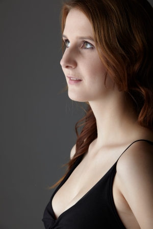 Young caucasian adult redhead woman with green eyes and very fair skin in a little black dress on a neutral grey background photo