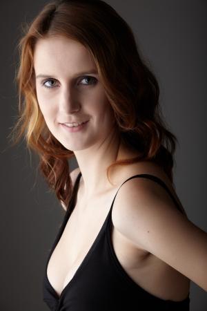 fair skin: J�venes adultos de raza cauc�sica mujer pelirroja de ojos verdes y piel muy blanca en un vestido negro sobre un fondo gris neutro