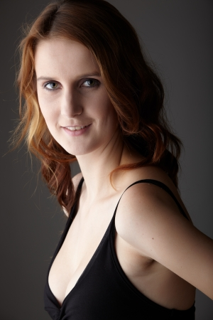Young caucasian adult redhead woman with green eyes and very fair skin in a little black dress on a neutral grey background Stock Photo - 13872201