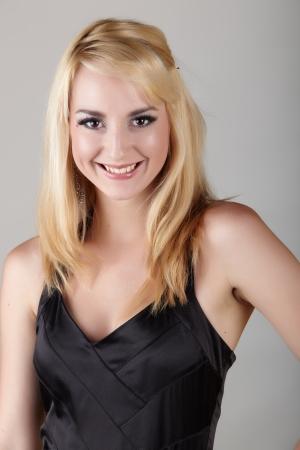 ojos marrones: Adultos j�venes de raza cauc�sica mujer con el pelo rubio y la joyer�a destacada sobre un fondo gris neutro con un peque�o vestido negro y grandes ojos marrones