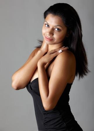 voluptuosa: Joven mujer voluptuosa para adultos de la India con el pelo largo y negro con un vestido negro sobre un fondo gris neutro