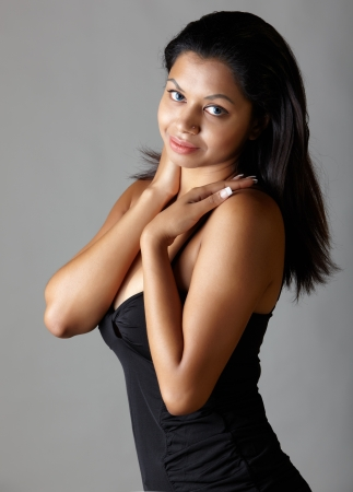 fuller figure: Young voluptuous Indian adult woman with long black hair wearing a black dress on a neutral grey background