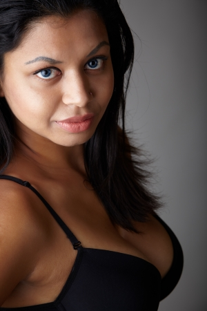 undressed: Young voluptuous Indian adult woman with long black hair wearing black lingerie on a neutral grey background Stock Photo
