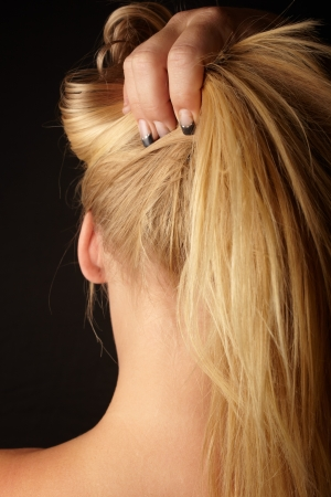 Nude Young adult caucasian woman holding her blonde hair up with one hand against a dark background and seen from behind Stock Photo - 14227644
