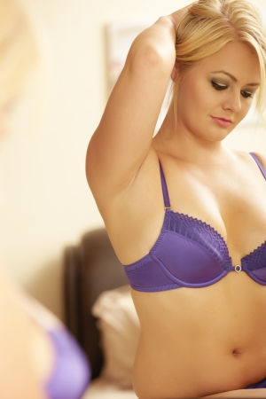 Young adult caucasian woman in purple lingerie looking at herself in a wall mirror while holding her blonde hair up with one hand  Stock Photo - 14227642