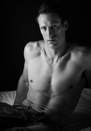 Extremely fit and handsome young caucasian adult man sitting on a bed against a dark wall wearing blue jeans and without a shirt  Black and White Stock Photo - 17343344