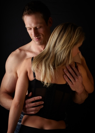 Young and fit caucasian adult couple in an embrace  Semi-nude and topless against a dark background with the woman wearing a sexy red and black lace corset   Stock Photo - 17343359