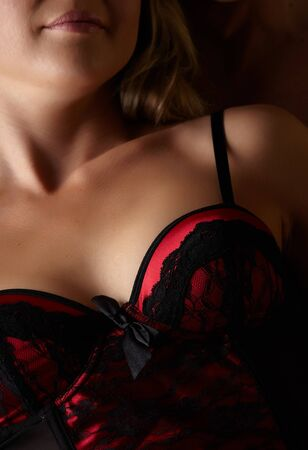 female sexuality: Young and fit caucasian adult woman in a sexy black and red lace corset against a dark background