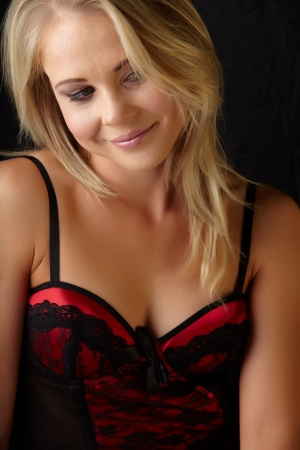 Young and fit caucasian adult woman in a sexy black and red lace corset against a dark background   photo