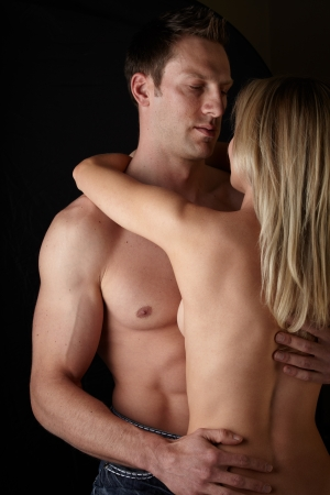 Young and fit caucasian adult couple in an embrace  Semi-nude and topless against a dark background