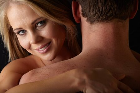 Young and fit caucasian adult couple in an embrace  Semi-nude and topless against a dark background Stock Photo - 17343406