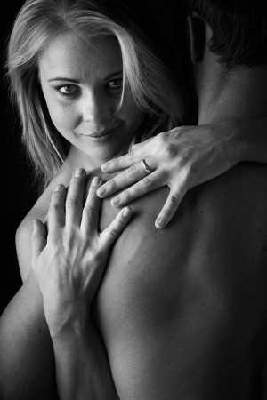 Young and fit caucasian adult couple in an embrace  Semi-nude and topless against a dark background  Black and White