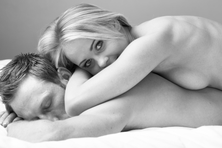Young and fit caucasian adult couple lying on naked on a bed  Black and White  photo