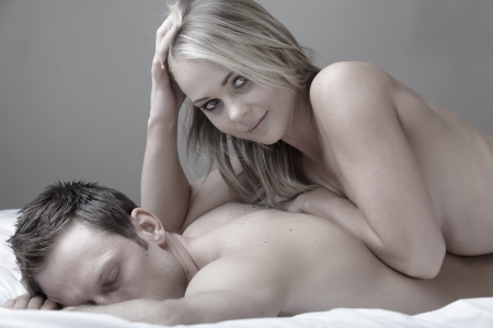 Young and fit caucasian adult couple lying on naked on a bed  Desaturated  photo