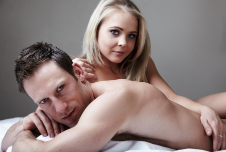Young and fit caucasian adult couple lying on naked on a bed   photo