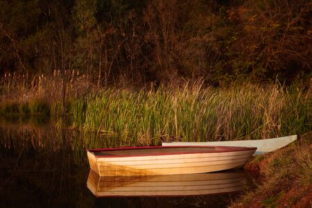 Tranquil scene of a small red and white fishing boat on a small rural pond at sunset with autumn foliage reflecting in the calm water   Stock Photo - 17347501